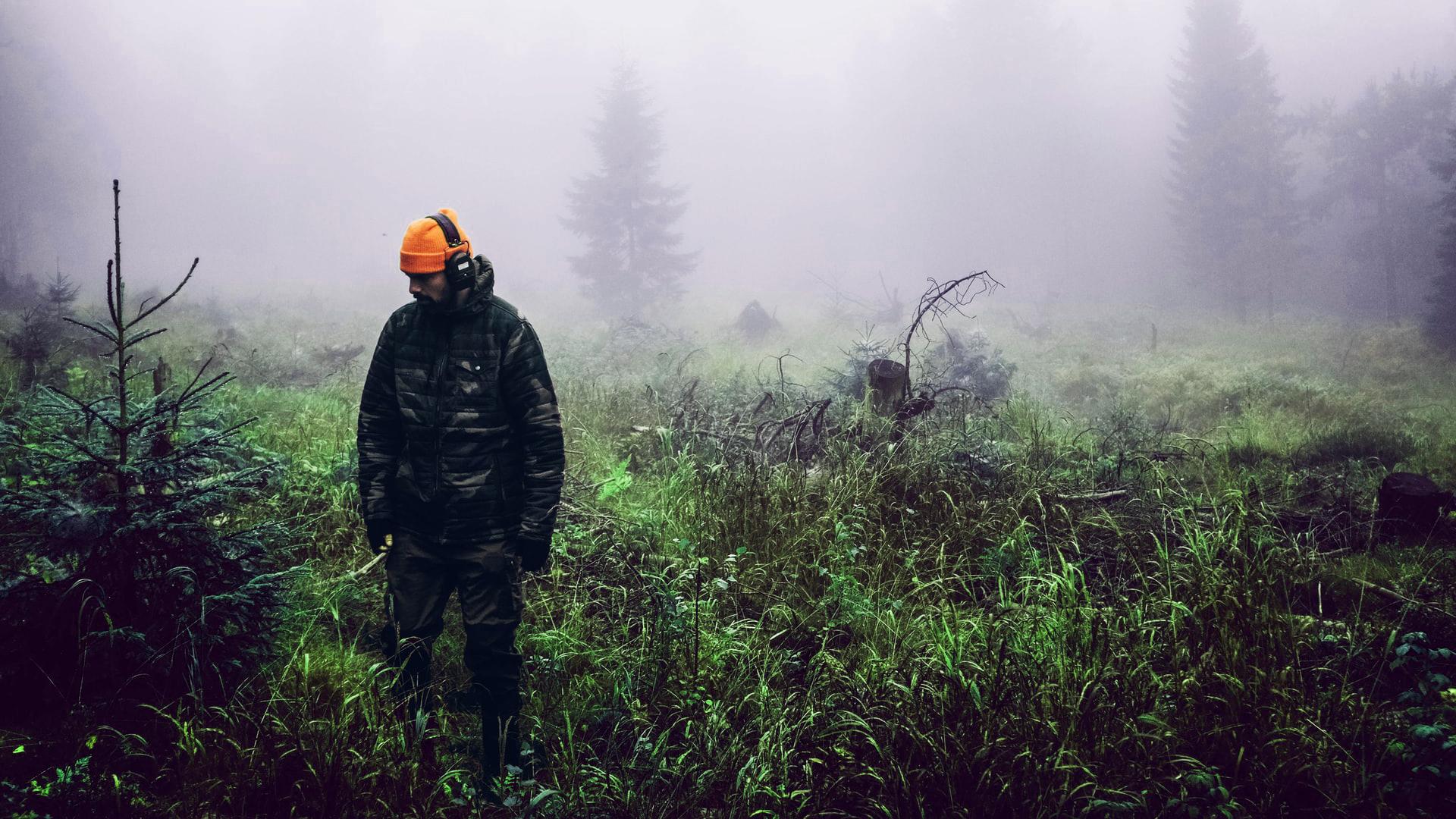 Jäger kontrolliert junge Bäume auf Verbiss